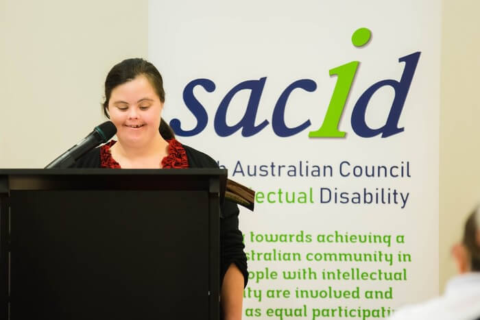 Bek stands speaking in a microphone with SACID banner behind