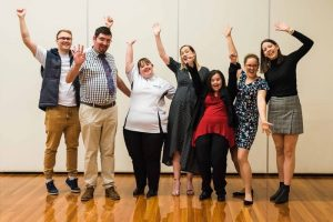 7 sacid staff are looking excited with their arms raised in celebration above their heads