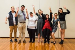 7 people stand with arms outstretched in celebration