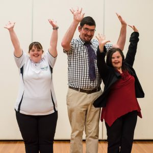 3 people stand with arms raised jumping happily into the air